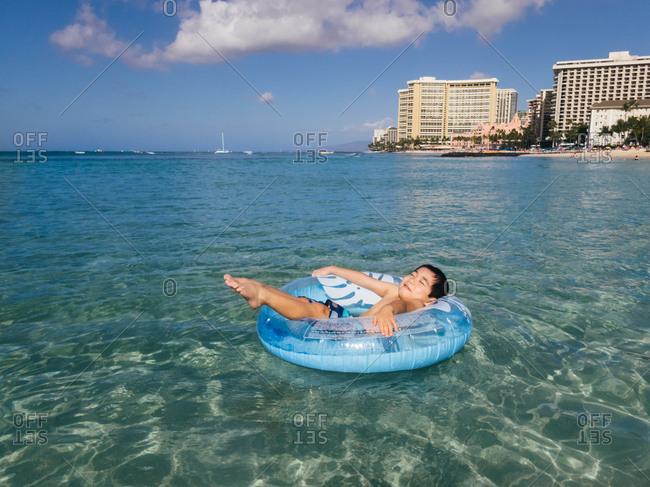 Boy relaxing in blue inflatable ring in Honolulu, Hawaii