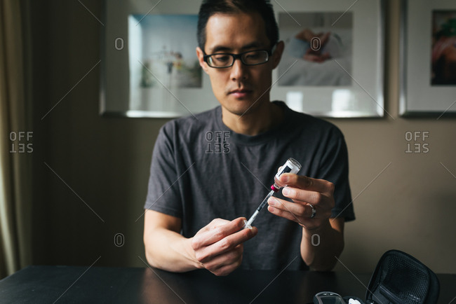Man preparing insulin syringe