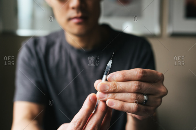Close up of a man preparing insulin syringe