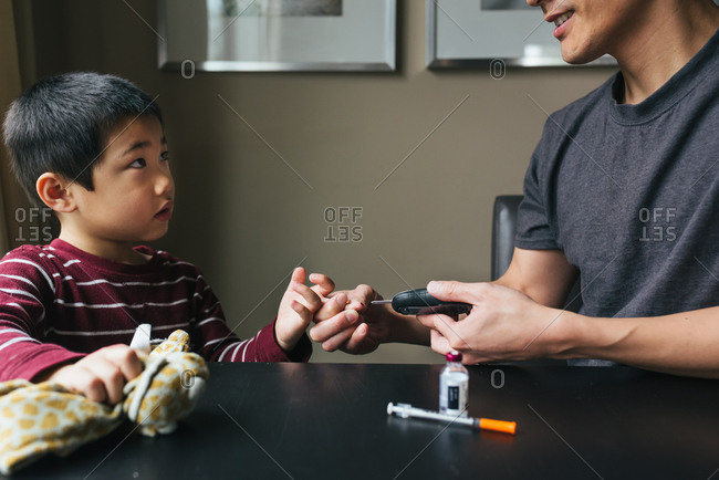 Man checking son's insulin levels