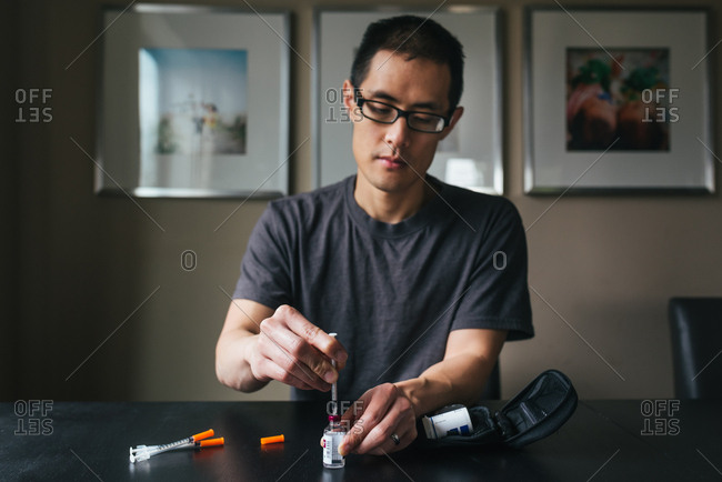 Man preparing syringe with insulin