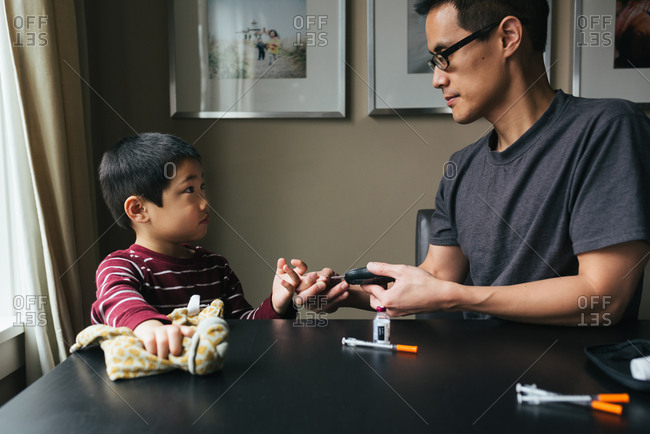 Man checking son's blood glucose levels
