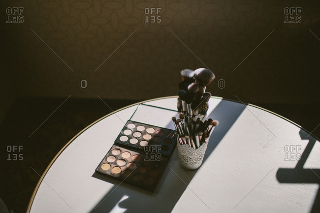 Makeup brushes and eye shadow palette in sunlight