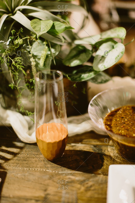 Dish of salsa on wooden table with plant centerpiece