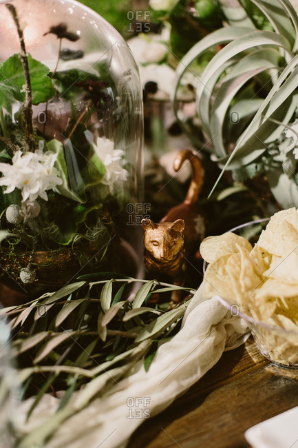 Table setting with greenery centerpiece and gold cat