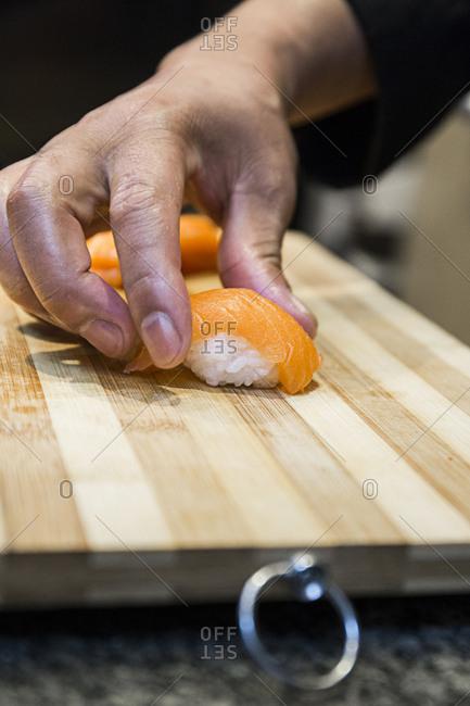 Chef making salmon nigiri sushi