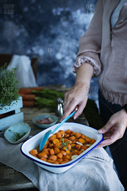 A woman cooking carrots in  pan