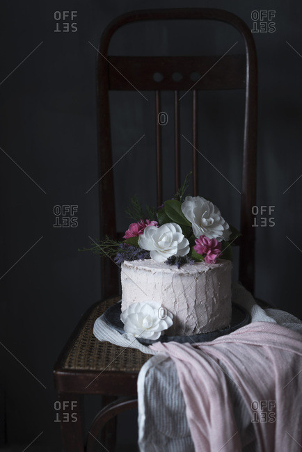 An iced cake decorated with flowers, on a chair