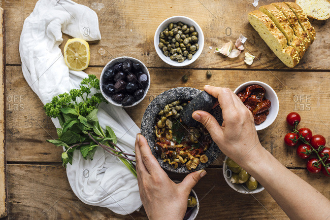 A woman mashing olives in a marble mortar to make olive tapenade is photographed from top view