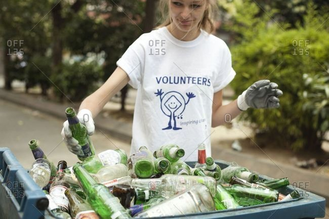 Naples, Italy - June 24, 2013: Volunteer cleaning up bottles