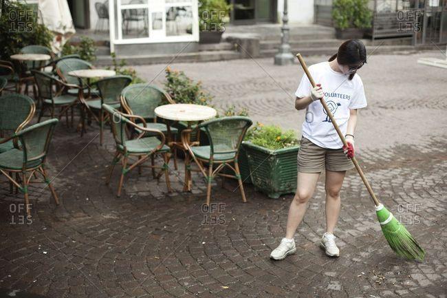 Naples, Italy - June 24, 2013: Volunteer sweeping up trash