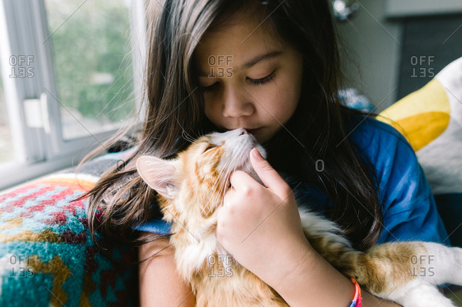 Young girl cuddling on sofa with orange cat