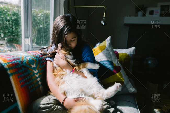 Young girl snuggling on sofa with orange cat