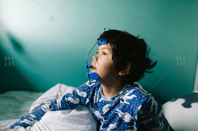 Boy in bed wearing his orthodontic headgear