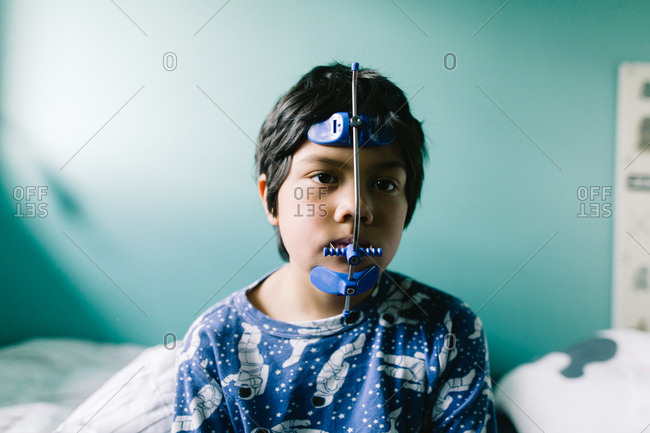 Boy sitting in bed wearing his orthodontic headgear