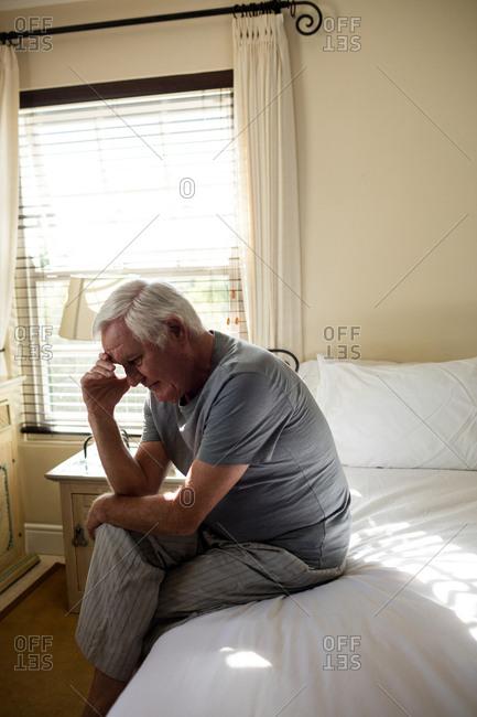 Worried senior man sitting on bed in the bedroom