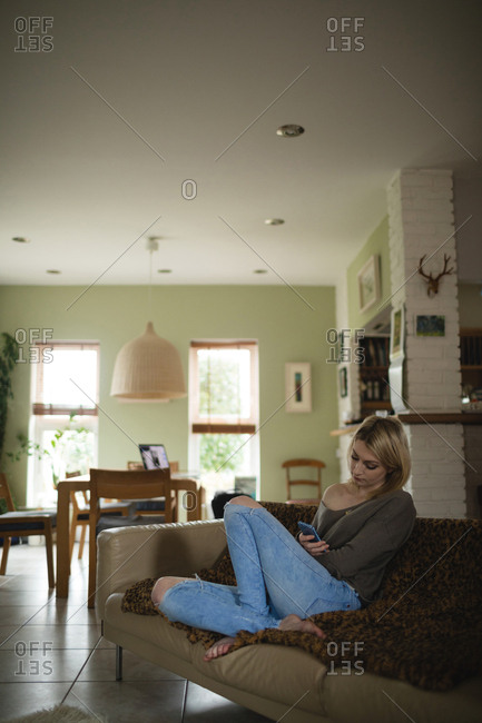 Woman sitting and using mobile phone on couch in living room