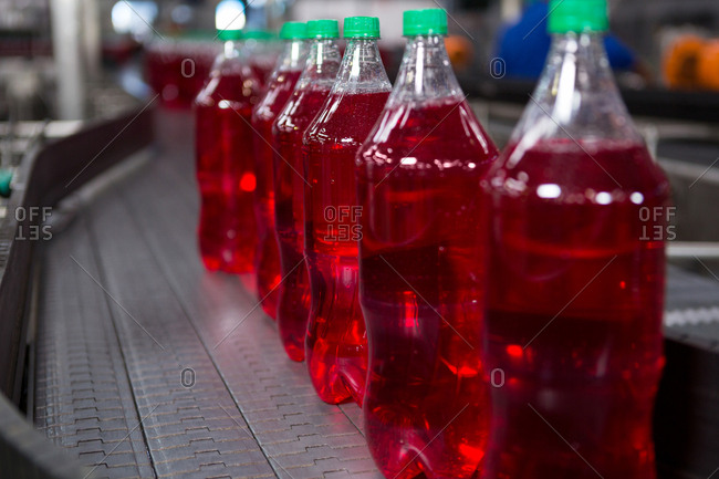 Red juice bottles on production line in factory