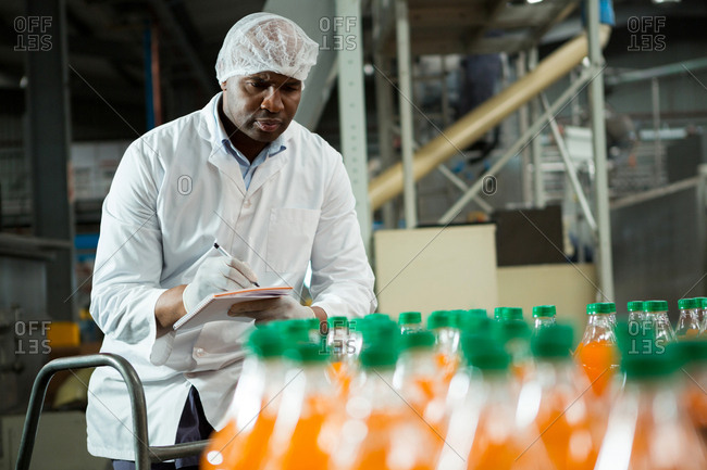 Male worker noting in juice factory