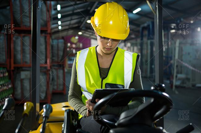 Female worker using digital tablet while sitting on forklift