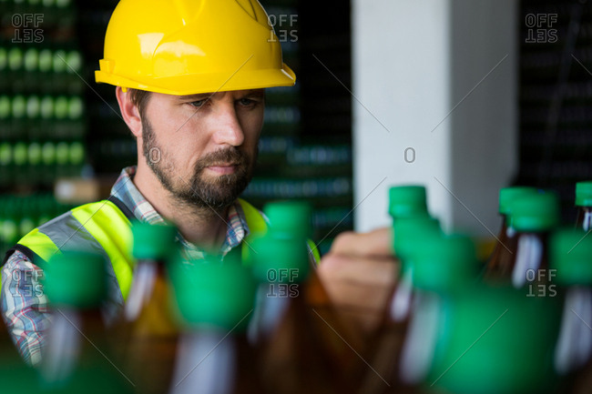 Man examining juice bottles in factory