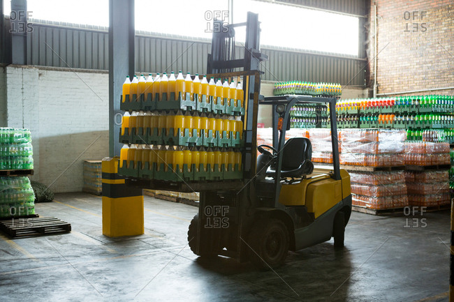 Packed juice bottles and forklift in distribution warehouse