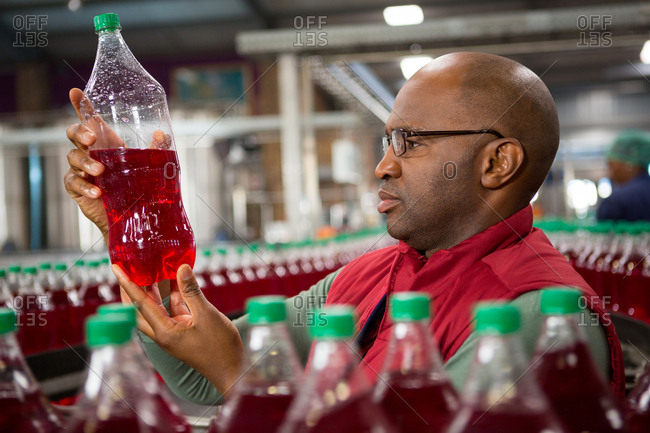 Male worker examining bottle in cold drink factory