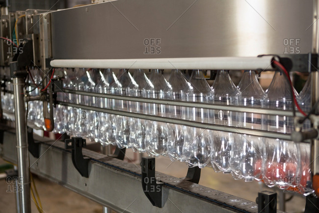 Empty bottles on production line in juice factory
