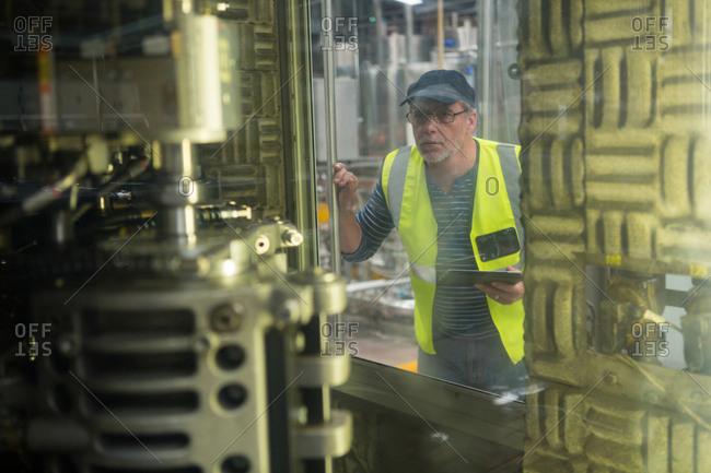 Employee watching machinery at juice factory