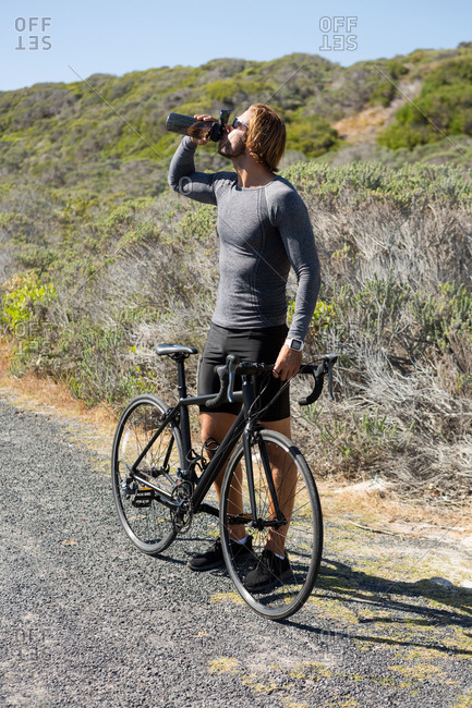 Athlete drinking water while standing by bicycle