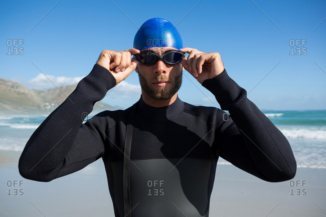 Athlete wearing swimming goggles by sea
