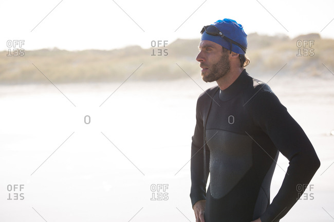 Thoughtful athlete standing on shore