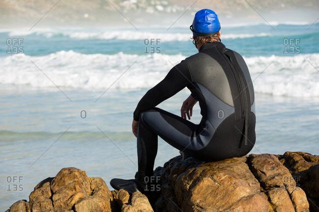 Athlete sitting on rock at sea shore