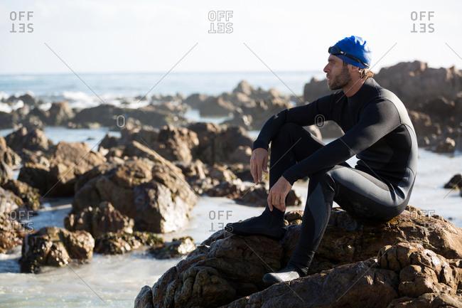Thoughtful athlete sitting on rock