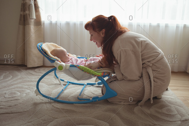 Mother with baby in rocking chair at home