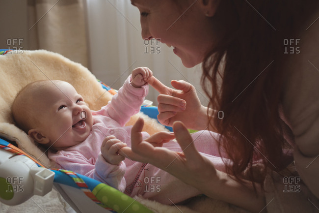 Cheerful mother playing with baby in rocking chair