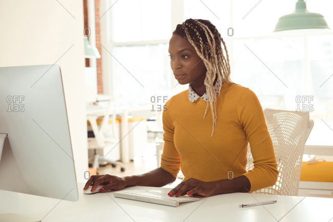 Female executive using laptop at desk