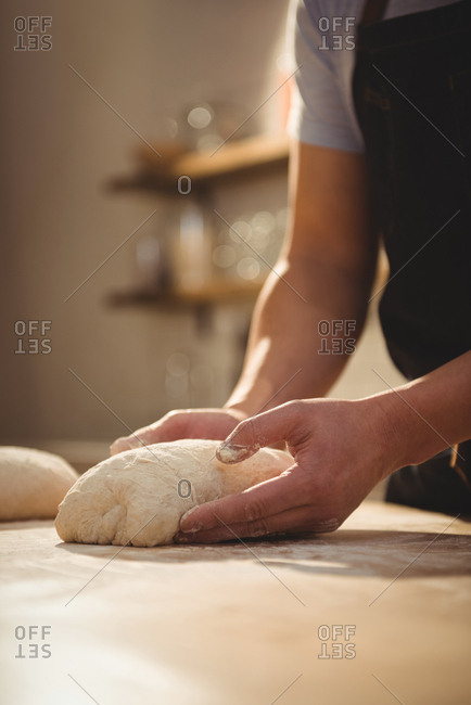 Chef kneading dough in professional kitchen