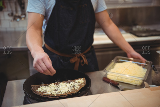 Chef adding grated cheese on pancake in commercial kitchen