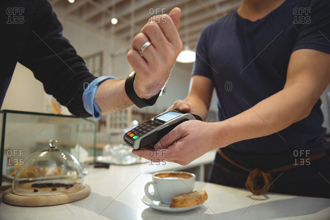 Customer paying with NFC technology on smart watch in coffee shop