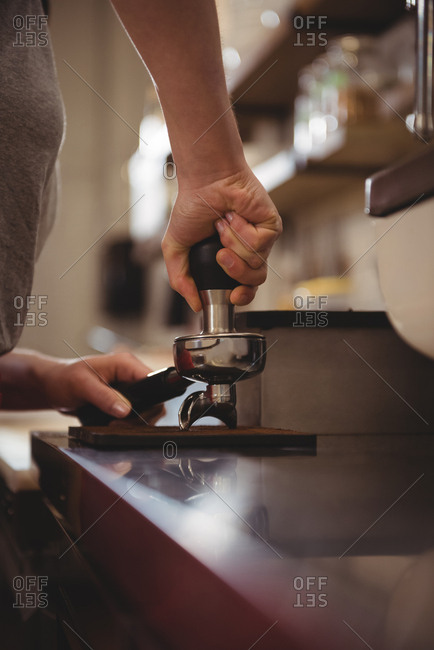 Female barista tamping coffee in cafe