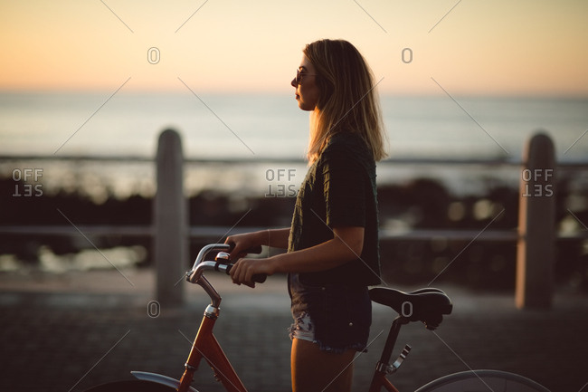 Woman standing with bicycle on street