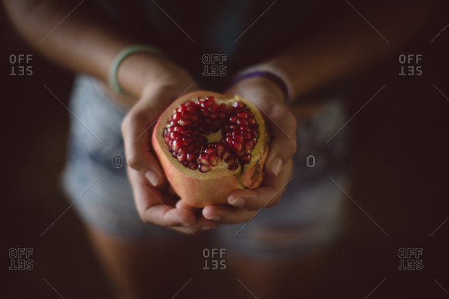Mid section of holding pomegranate