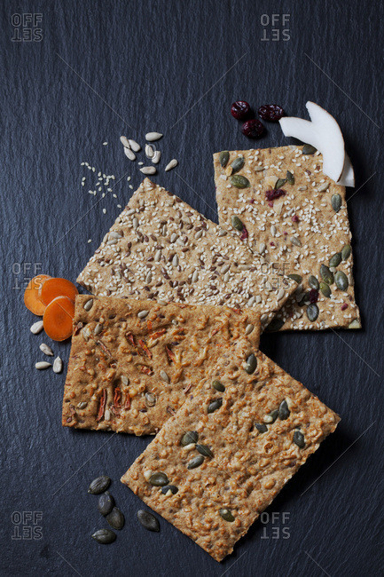 Four various slices of grain crisp breads and ingredients on slate