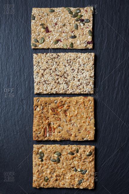 Row of four various slices of grain crisp breads on slate