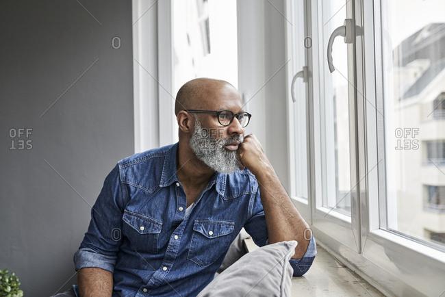 Mature man sitting at window- looking worried