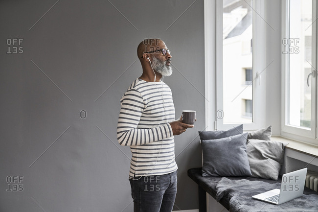 Mature man with earphones drinking coffee
