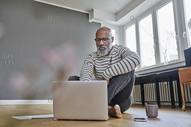 Mature man sitting on floor- working on laptop