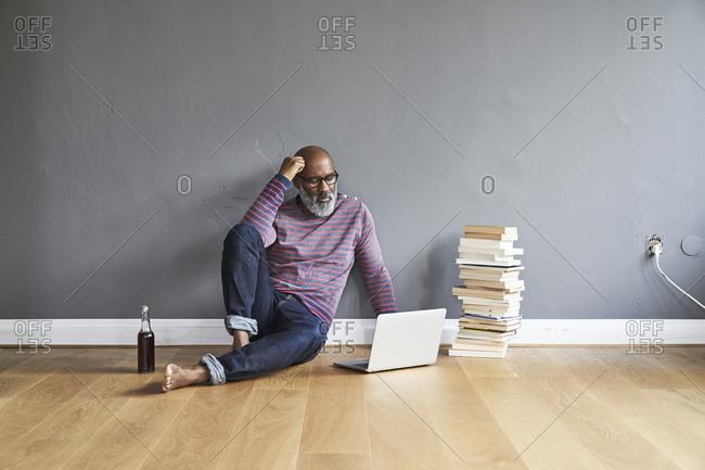 Mature man sitting on floor- using laptop