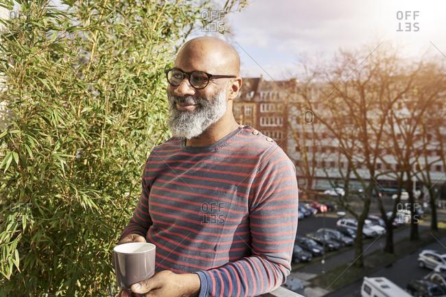 Mature man standing on balcony- drinking coffee